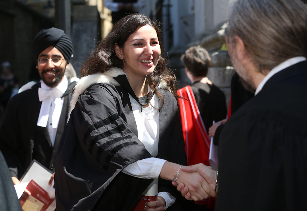 A student smiles and shakes hands with an academic on her graduation day