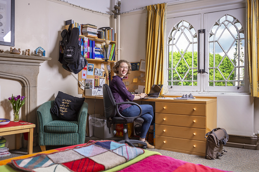 A student sits in her room at her desk