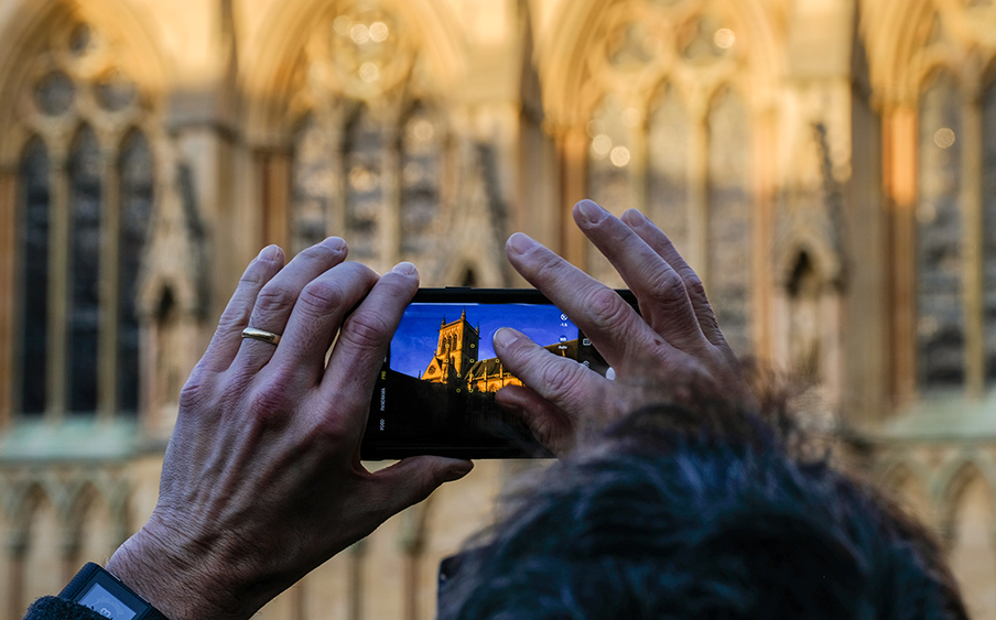 A visitor takes a photo of the College Chapel on his phone