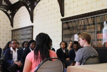 Pupils from La Retraite School listen attentively to St John's College students