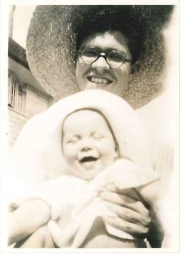 Photograph of Fred with his new son Geoff in 1944