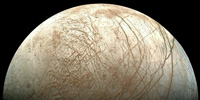 Europa, moon of Jupiter, is thought to hide a sea of liquid water beneath its icy surface. Could an extraterrestrial ecosystem thrive in this dark alien ocean? © NASA