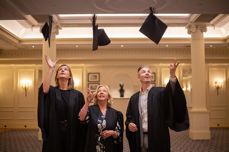 Three people throw mortar boards into the air