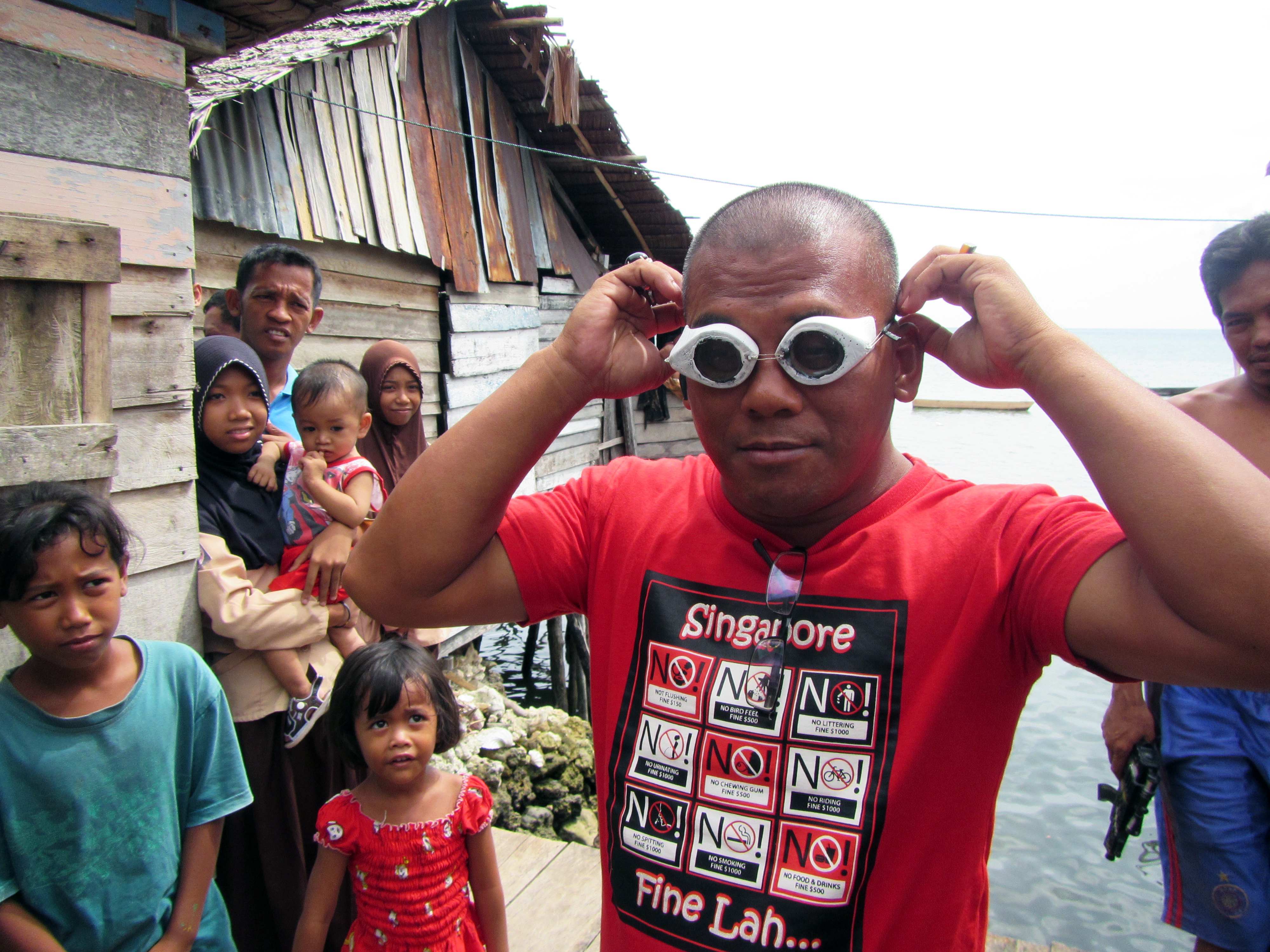 A Bajau villager demonstrates the use of traditional wooden goggles