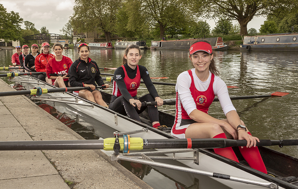 Rowers sit in a boat on the river Cam