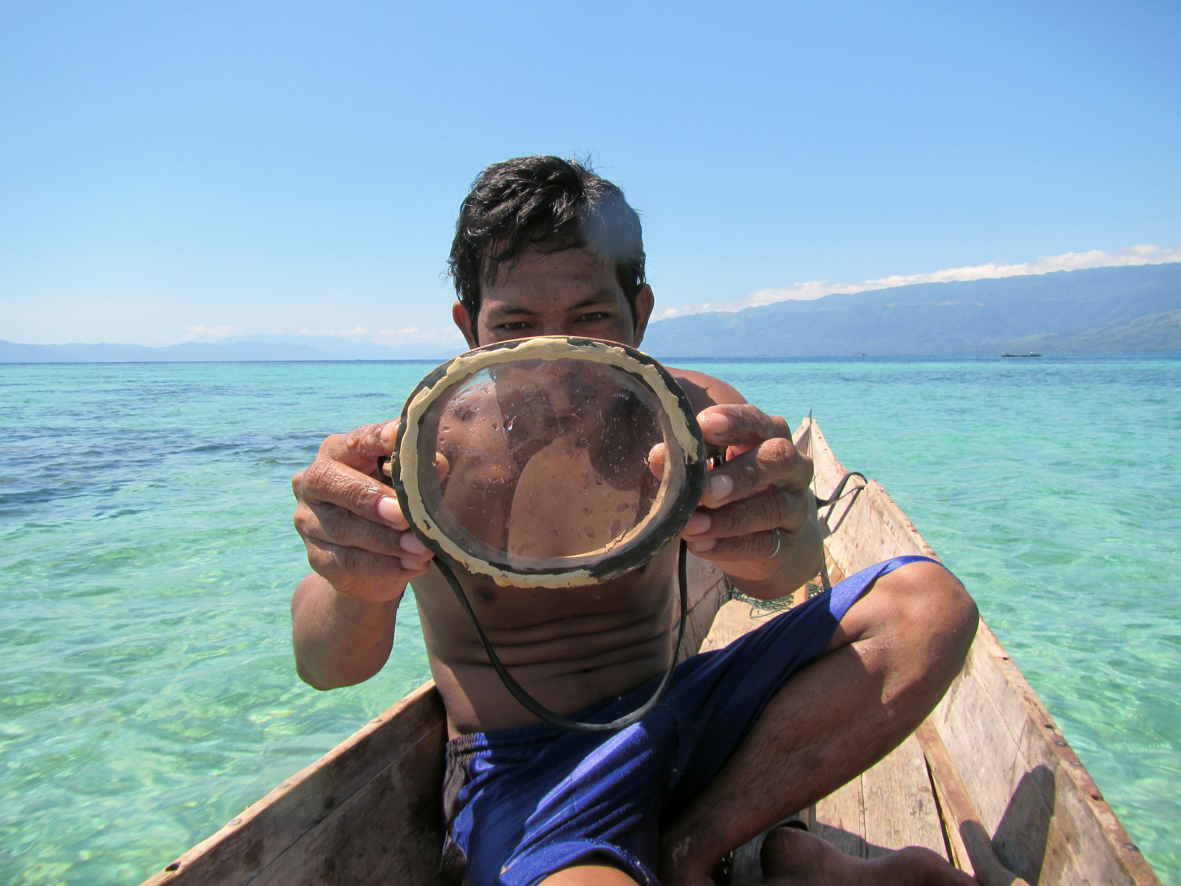 A Bajau diver displays a traditional wooden diving mask.